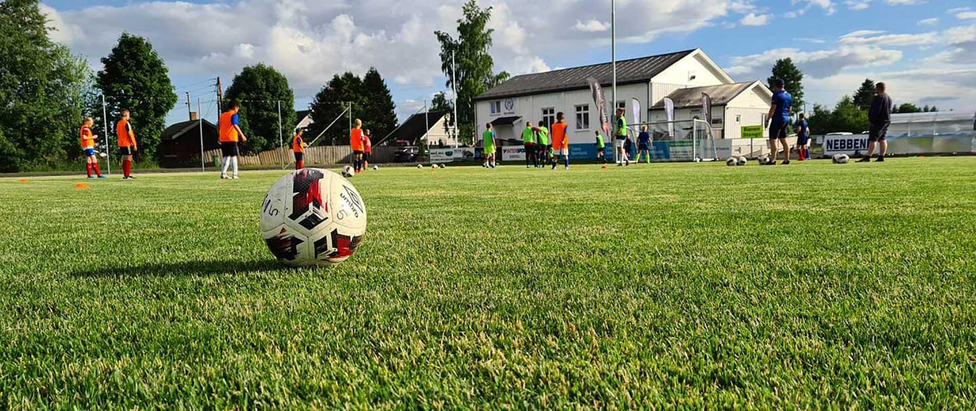 Fotball på gressbane, medn Bøn Klubbhus i bakgrunnen