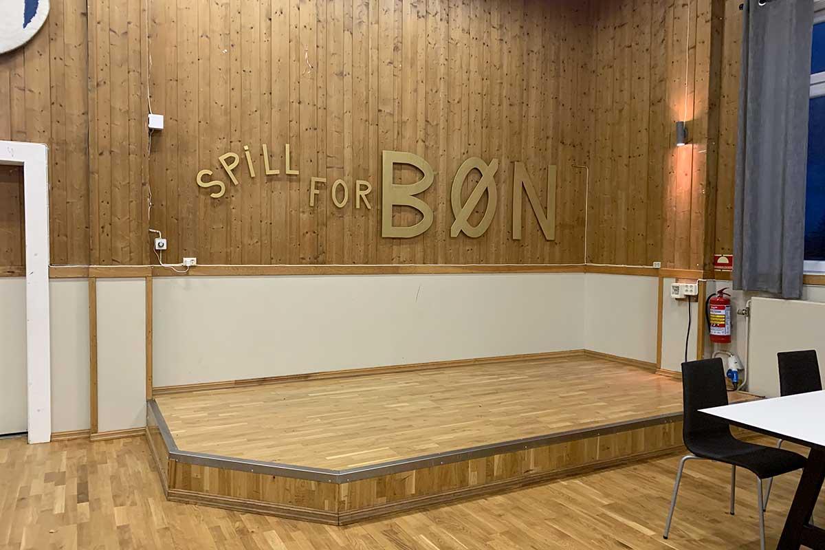 """Scenen i salen i Bøn KLubbhus, med ordene """"Spill for Bøn"""" på veggen"""